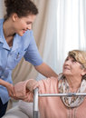 Careful young physiotherapist female and older disabled woman Stock Photos