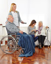 Caregiver entertaining senior citizens in a retirement home Royalty Free Stock Images