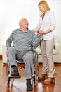 Caregiver helping senior citizen smiling men in wheelchair standing up Stock Image