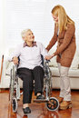 Caregiver helping senior woman citizen women in a wheelchair at home Stock Images