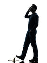 Careless man walking silhouette one on the telephone in studio on white background Stock Image