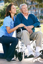 Carer Pushing Senior Man In Wheelchair Royalty Free Stock Image
