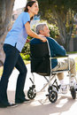 Carer Pushing Senior Man In Wheelchair Royalty Free Stock Images