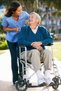 Carer Pushing Senior Man In Wheelchair Royalty Free Stock Photography