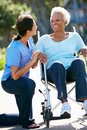 Carer Pushing Senior Woman In Wheelchair Royalty Free Stock Photos