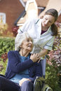 Carer pushing senior woman in wheelchair female Royalty Free Stock Images