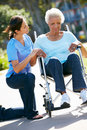 Carer Pushing Unhappy Senior Woman In Wheelchair Royalty Free Stock Photo