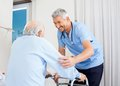 Caretaker helping senior man to use walking frame smiling male men in bedroom at nursing home Royalty Free Stock Photo
