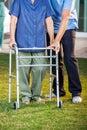 Caretaker helping senior woman in using walking low section of male women frame at nursing home lawn Royalty Free Stock Photos