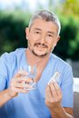 Caretaker holding blister pack and glass of water portrait male nurse at nursing home porch Stock Photo