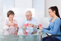Caretaker playing cards with senior couple young female at table in nursing home Royalty Free Stock Images