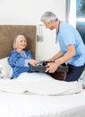 Caretaker serving breakfast to senior woman on bed male women in nursing home Stock Photos