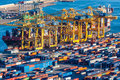 Cargo containers and vessel big is unloaded with cranes in terminal located in barcelona Royalty Free Stock Images