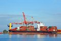 Cargo crane and ship container stack under bridge Stock Photo