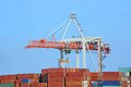 Cargo crane and ship container stack under bridge Royalty Free Stock Photos