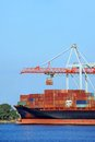Cargo crane and ship container stack under bridge Royalty Free Stock Photo