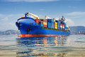 Cargo ship full of containers blue container anchored in harbour Royalty Free Stock Photos