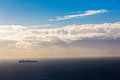 Cargo ship loaded with cargo containers heads south with the sunrise from the rear photo image overlooking the ocean and sea blue Stock Image