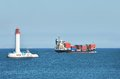 Cargo ship near lighthouse Stock Images