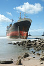 Cargo ship run aground on rocky shore Royalty Free Stock Photo