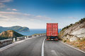Cargo truck on the mountain highway with blue sky and sea a background Stock Image