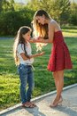 Photo : Caring and beautiful long-haired mother in cocktail red dress wipes her daughter`s face with wet napkins in the park in  umbrella a