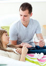 Caring man giving sick girlfriend pills and water Royalty Free Stock Image