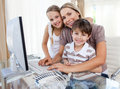 Caring mother and her children at a computer Royalty Free Stock Images