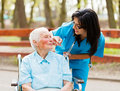 Caring nurse outdoors helping elderly lady in wheelchair Royalty Free Stock Images
