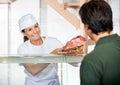 Carnicero selling fresh meat al cliente Foto de archivo