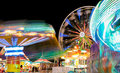 Carnival and Ferris Wheel at Night Spinning Lights
