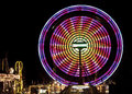 Carnival ferris wheel pink and yellow against a black background and lights Royalty Free Stock Photos