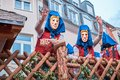 stock image of  Carnival figures on a cart with wooden fence.