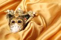 Carnival mask lying on a yellow silk Royalty Free Stock Photos