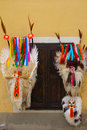 Carnival masks hanging on the wall traditional kurenti from ptuj slovenia made of ship skins horns and long red tongues by Stock Photos