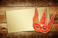 Carnival red mask with old paper for greeting on wooden background Stock Photos