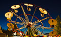 Carnival sunset umbrella ride many carnivals operate after with lots of lights Stock Photo
