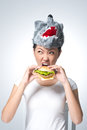 Carnivorous vertical image of a girl in a wolf mask devouring a hamburger Royalty Free Stock Image