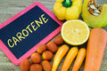 Carotene in orange color fruits and vegetables written on chalkboard with Royalty Free Stock Image