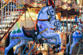 Carousel horses brightly painted at an amusement park Stock Photos