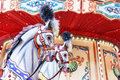 Carousel horses on a vintage carnival merry go round retro g closeup of colorful roundabout with Stock Photos