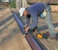 Carpenter applying caulk to ridge vent Stock Photos