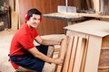 Carpenter arranging wooden planks in workshop portrait of confident young Royalty Free Stock Photos