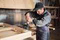 Carpenter assembles wooden furniture, focus on the hand drill Royalty Free Stock Photo