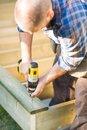 Carpenter building deck using cordless drill while Stock Images
