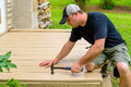 Carpenter bulding deck swinging hammer a in plain black shirt and hat a and a Stock Photography