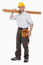 A carpenter carrying planks. Stock Images