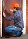 Carpenter changing lock in heavy metal door Royalty Free Stock Photo