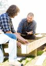 Carpenter communicating with coworker measuring mid adult wooden frame at construction site Royalty Free Stock Images