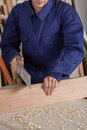 Carpenter cutting a piece of wood Royalty Free Stock Photo